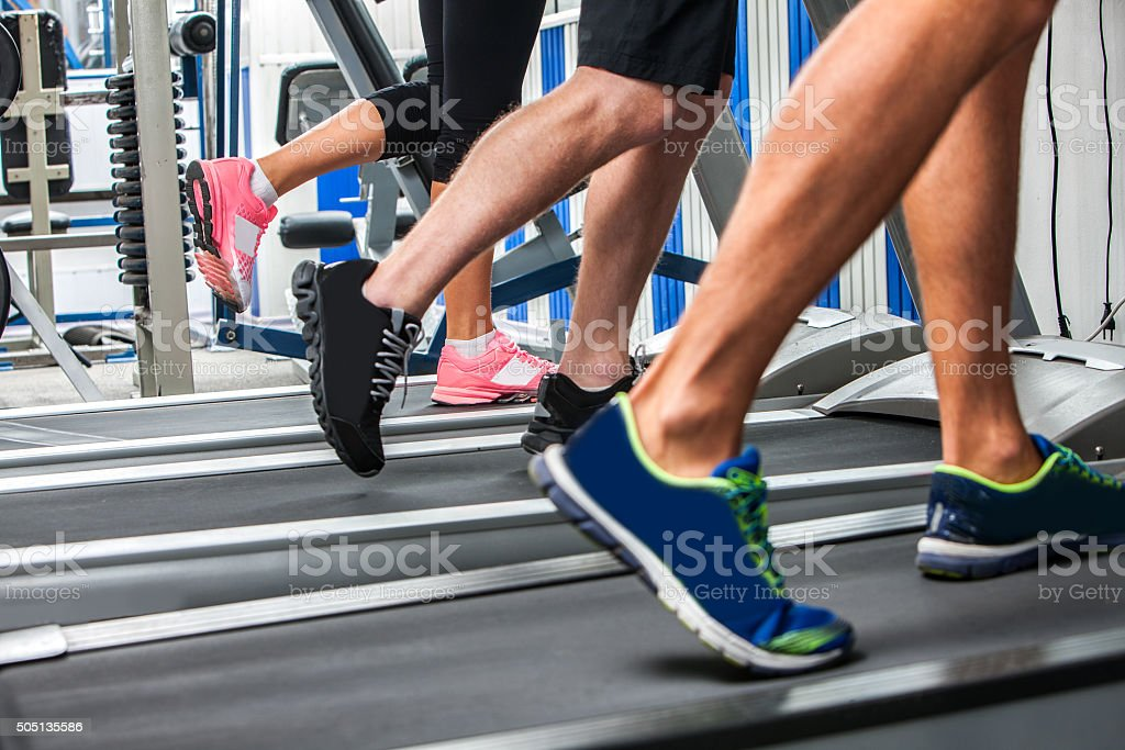 Group of legs wearing sneakers running on treadmill stock photo