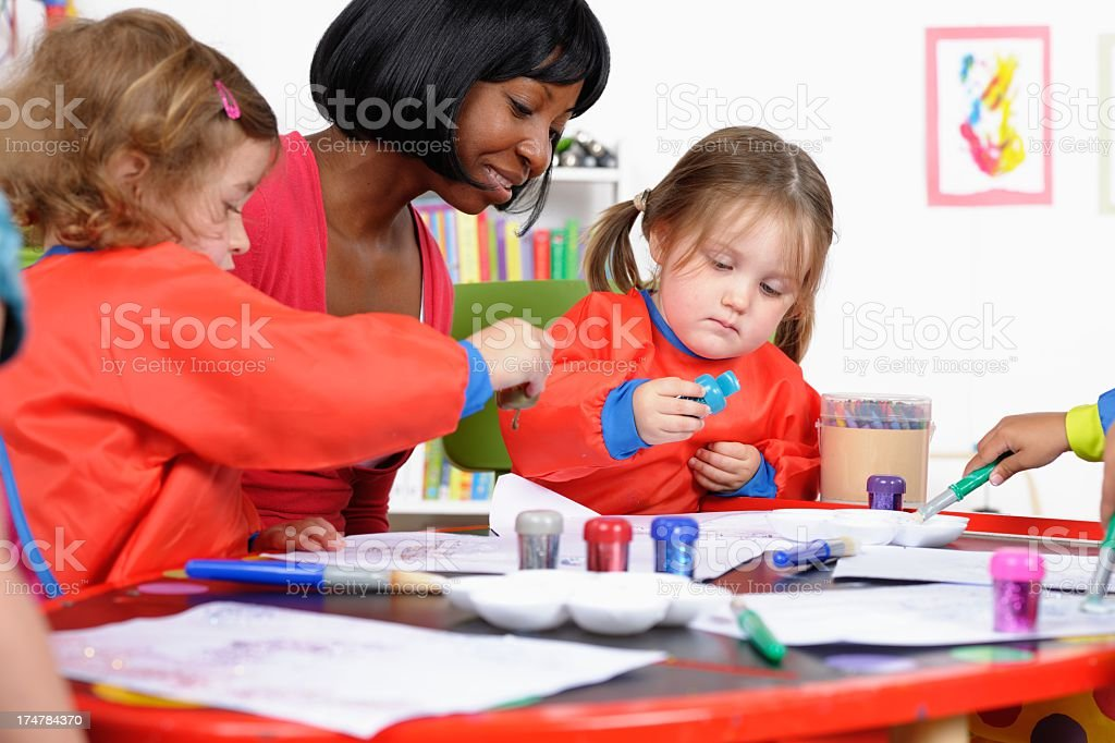 Group Of Little Children Enjoying Art And Craft With Carer royalty-free stock photo