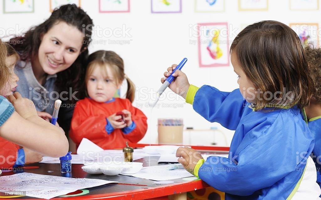 Group Of Little Children Using Glue To Create Art stock photo