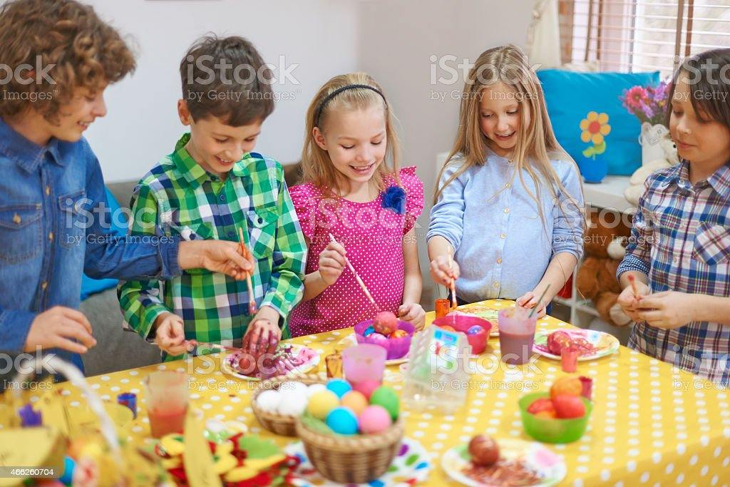 Group of little friends have fun with painting Easter eggs stock photo