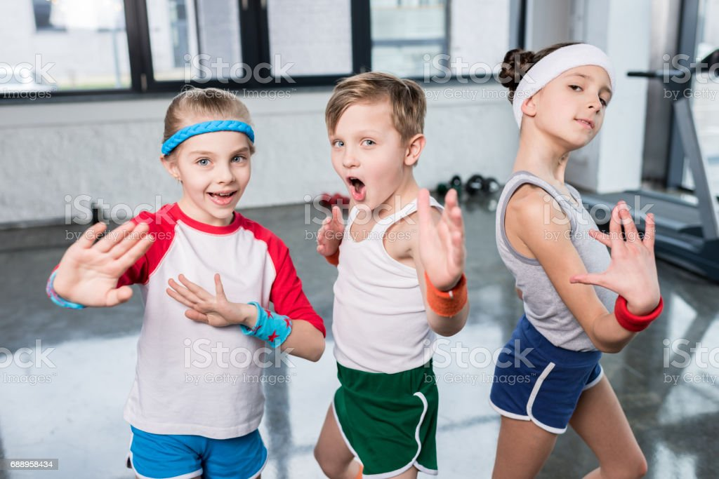 Group of little kids in sportswear exercising and posing at camera in gym, children sport school concept stock photo