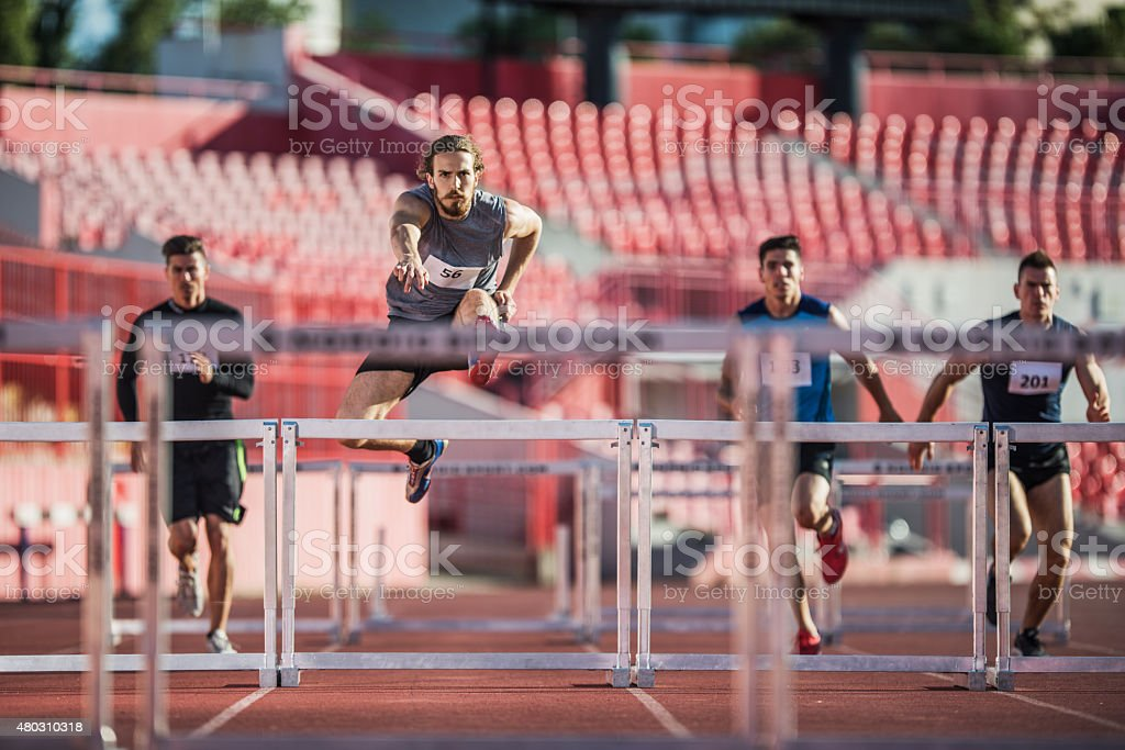 Group of male athletes jumping hurdles on a race. stock photo