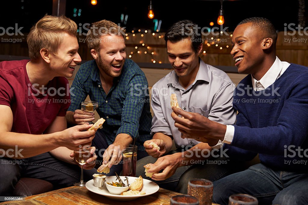 Group Of Male Friends Enjoying Night Out At Rooftop Bar stock photo