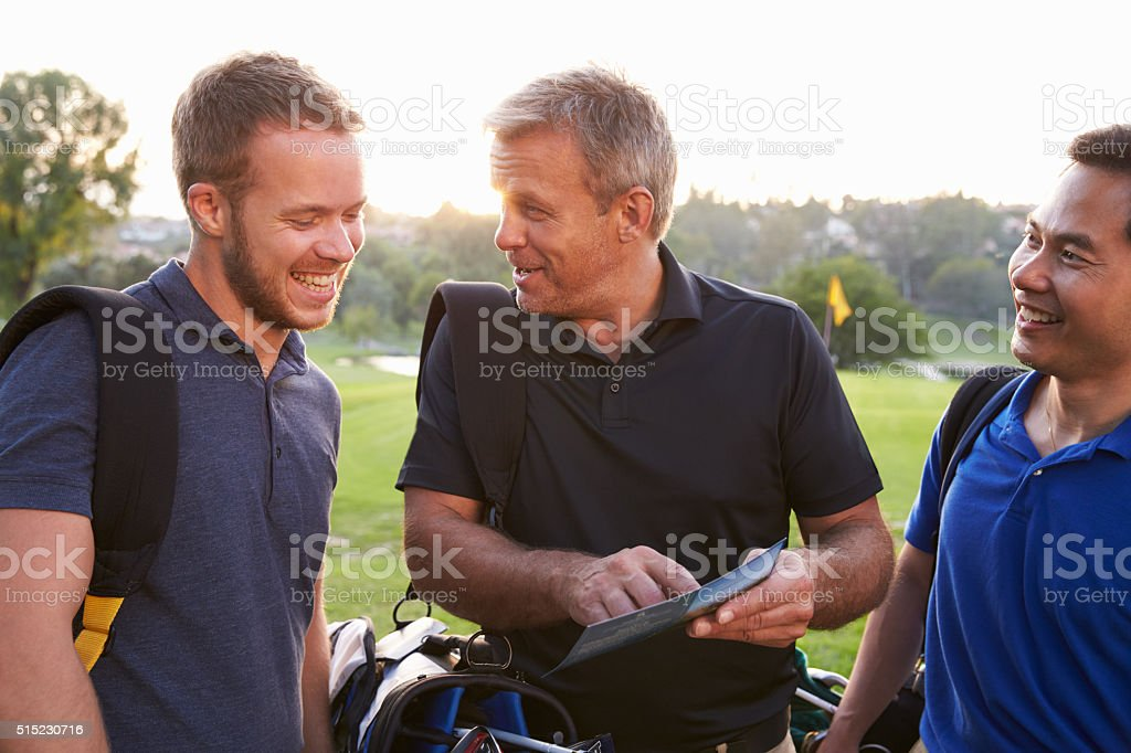 Group Of Male Golfers Marking Scorecard At End Of Round stock photo