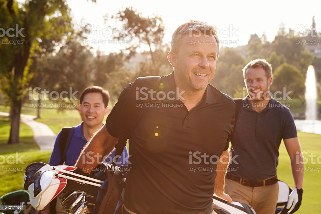 Group Of Male Golfers Walking Along Fairway Carrying Bags stock photo