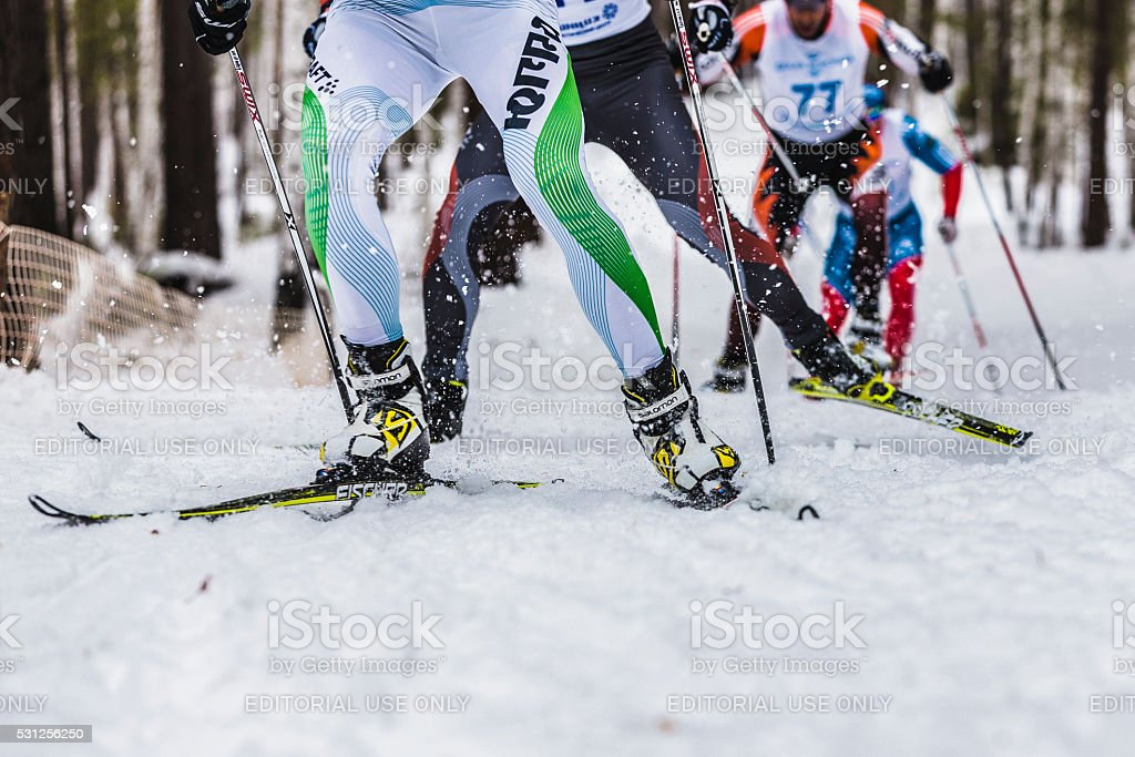 group of male skiers going uphill front view stock photo
