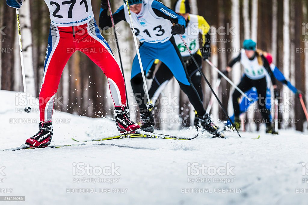 group of male skiers going uphill stock photo