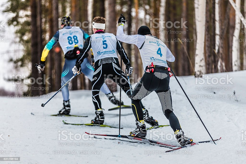 group of male skiers going uphill view from back stock photo