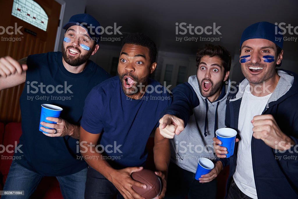 Group Of Male Sports Fans Watching Game On Television stock photo