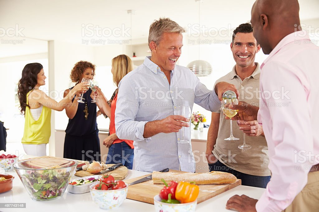 Group Of Mature Friends Enjoying Dinner Party At Home stock photo