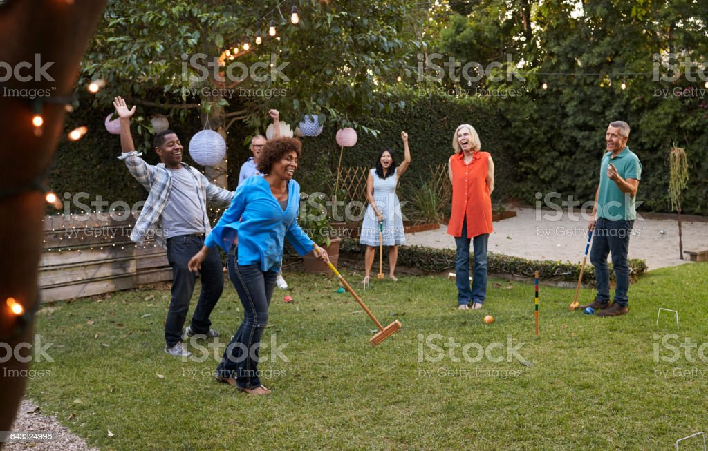 Group Of Mature Friends Playing Croquet In Backyard Together stock photo