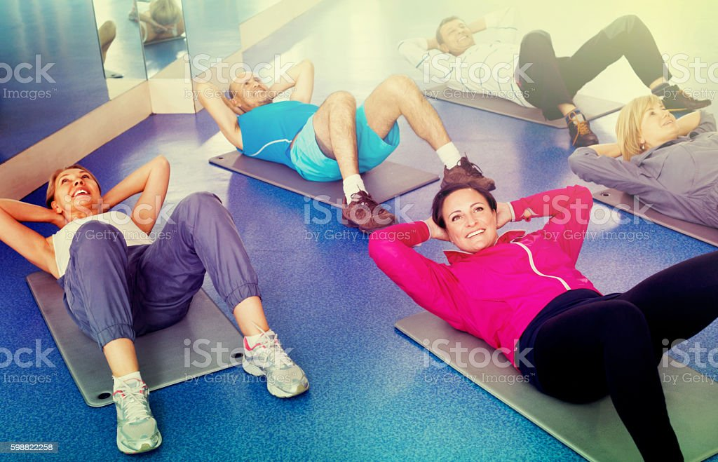 Group of mature people exercising on sport mats stock photo