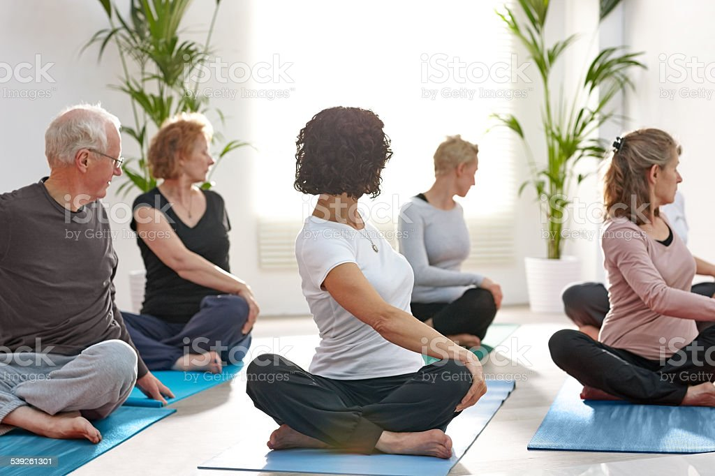 Group of mature people practicing yoga stock photo