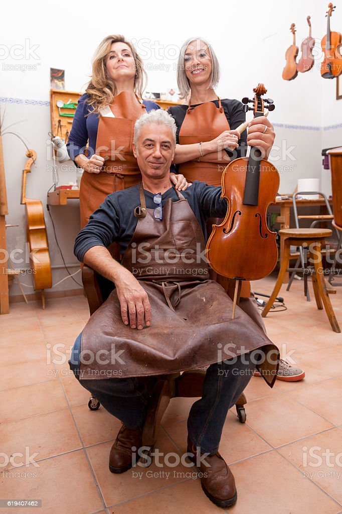 group of mature violin maker in pose stock photo