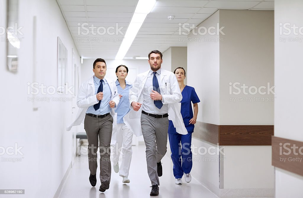 group of medics walking along hospital stock photo