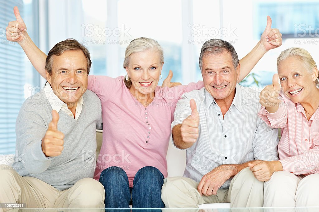 Group of men and women gesturing thumbs up sign stock photo