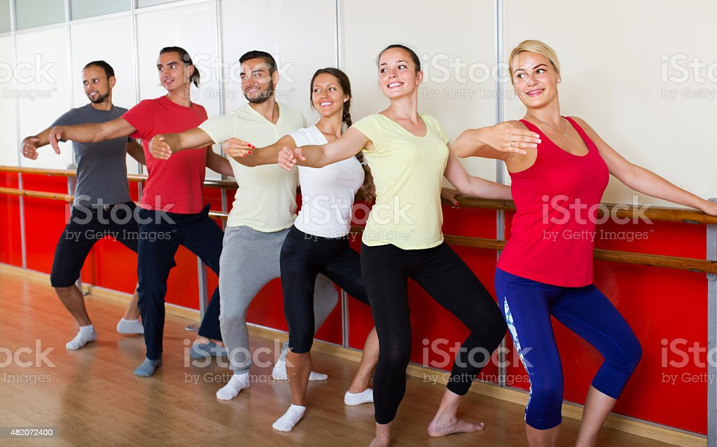 Group of  men and women practicing at the ballet barre stock photo