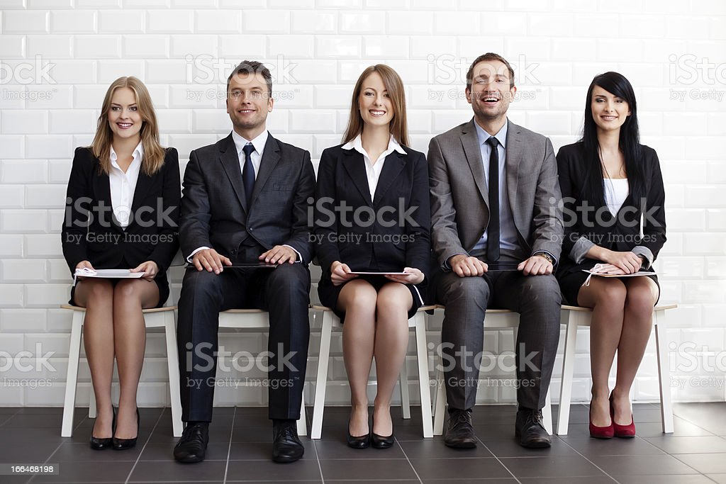 Group of men and women sitting on chairs royalty-free stock photo