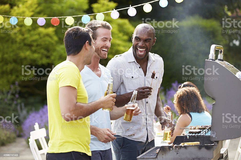 Group Of Men Cooking On Barbeque At Home stock photo