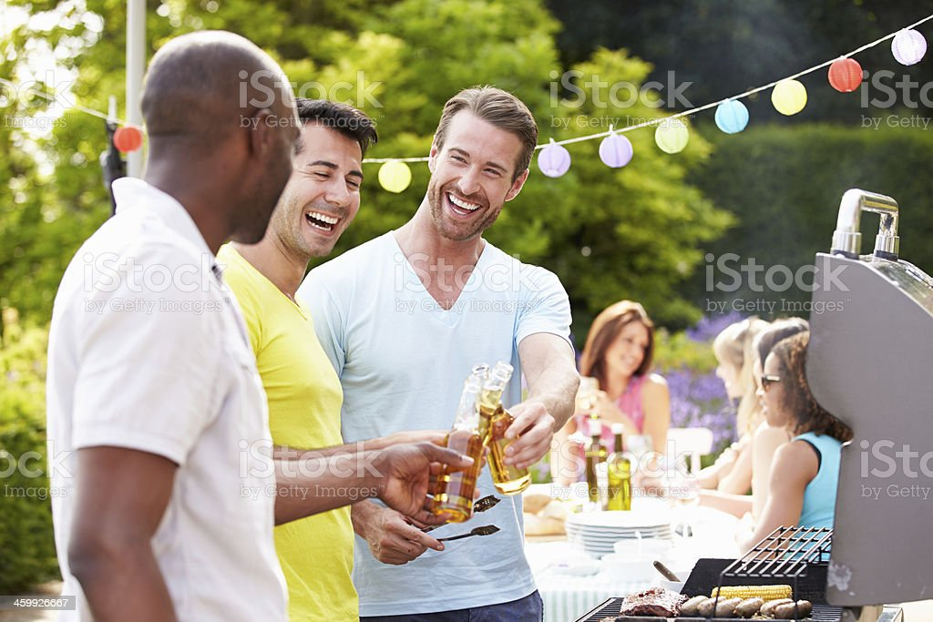 Group Of Men Cooking On Barbeque At Home royalty-free stock photo