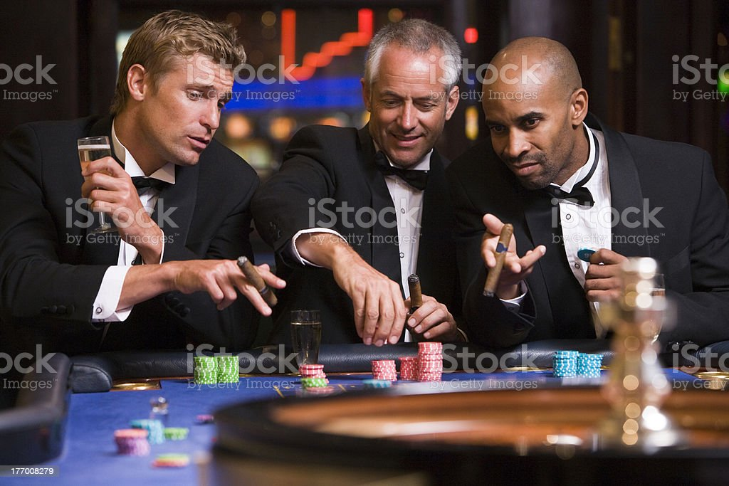 Group of men gambling at roulette table stock photo
