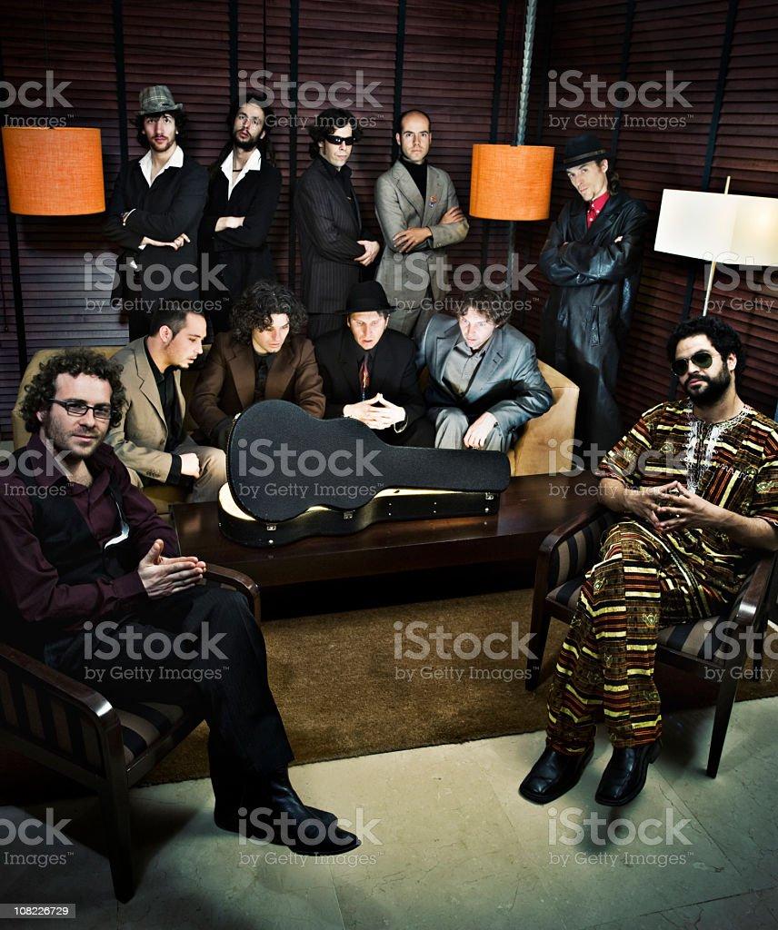 Group of Men Huddled Around Guitar Case stock photo