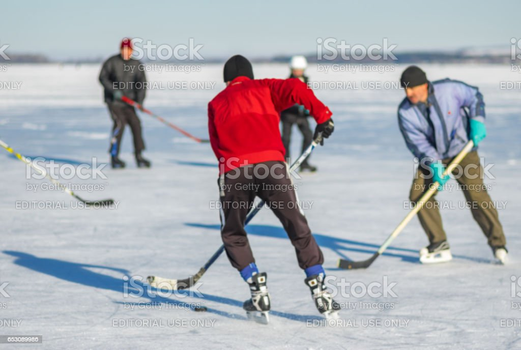Group of men playing hockey on a frozen river Dnepr in Ukraine stock photo