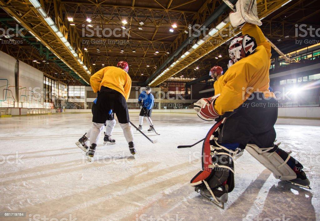 Group of men playing ice hockey at ice hockey stadium. stock photo