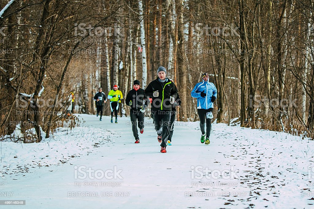 group of men running on winter alley stock photo