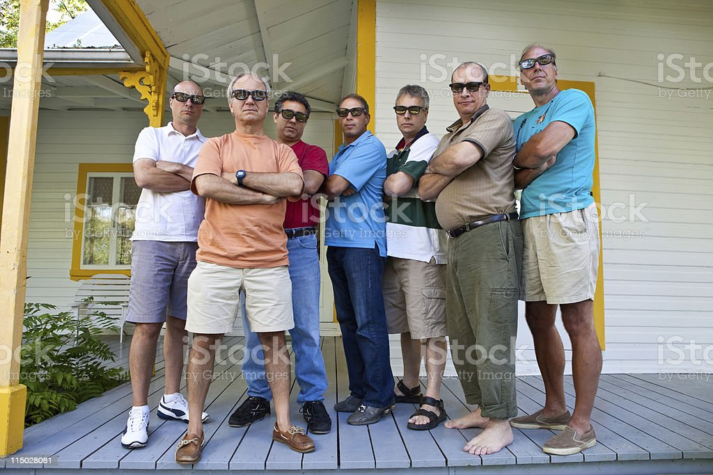 Group of men standing with arms folded on porch stock photo