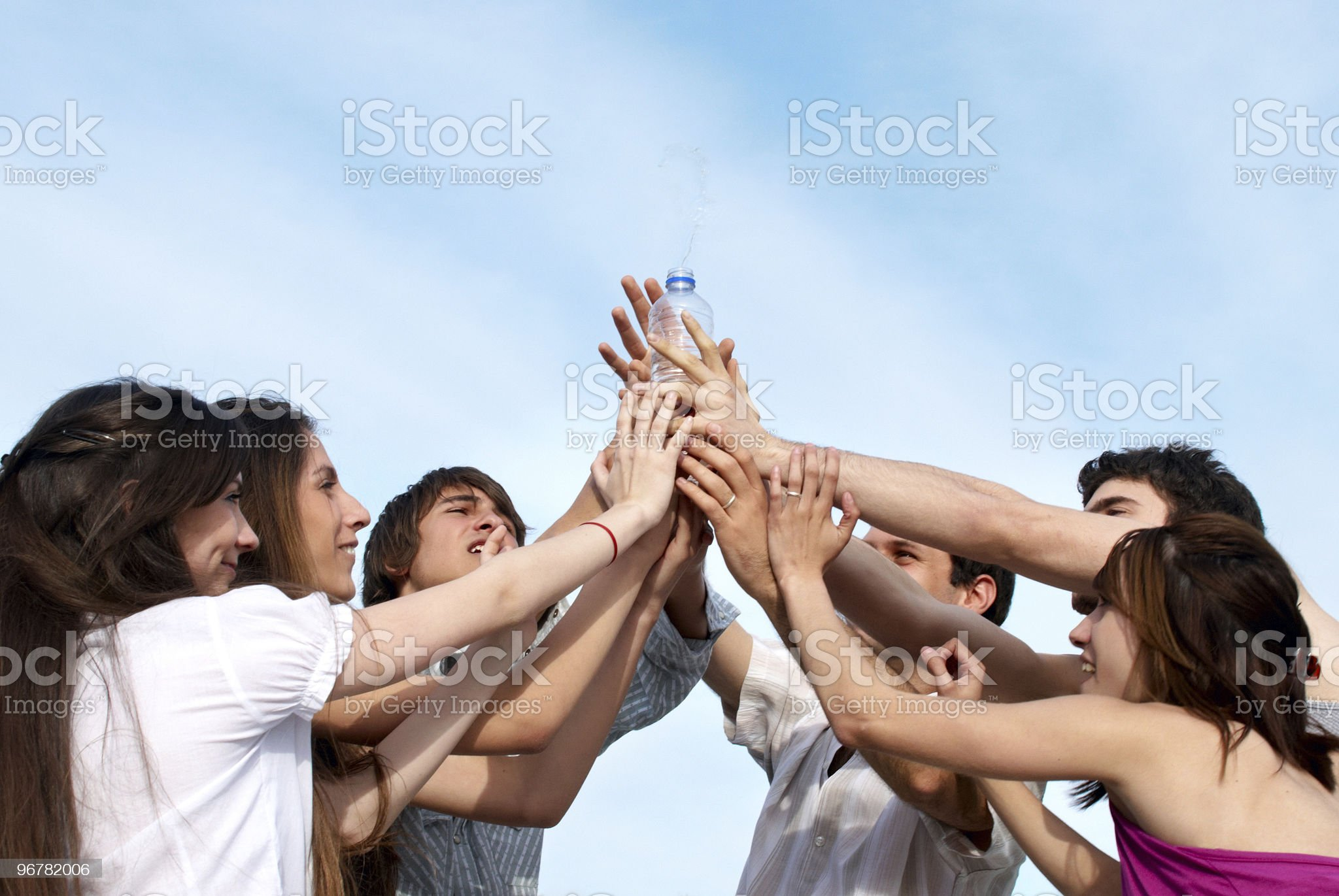 Group of men stretching hands to a bottle with water royalty-free stock photo