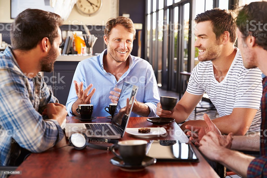 Group of men talking at a coffee shop stock photo