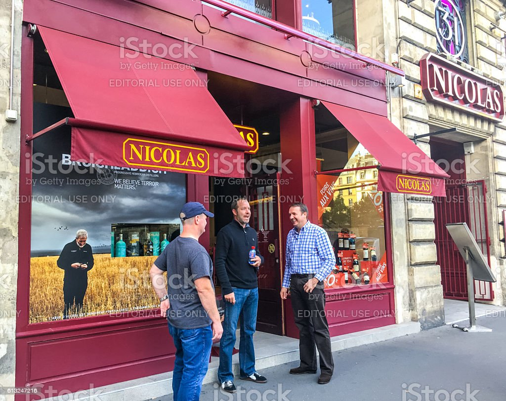 Group of men talking near Nicolas wine shop, Paris stock photo