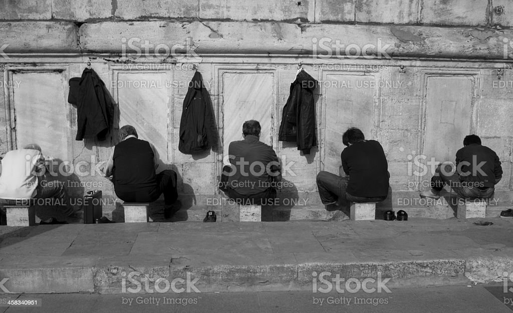 Group of men washing feet and faces royalty-free stock photo
