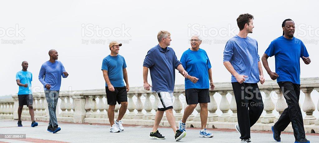 Group of men wearing blue shirts, power walking stock photo