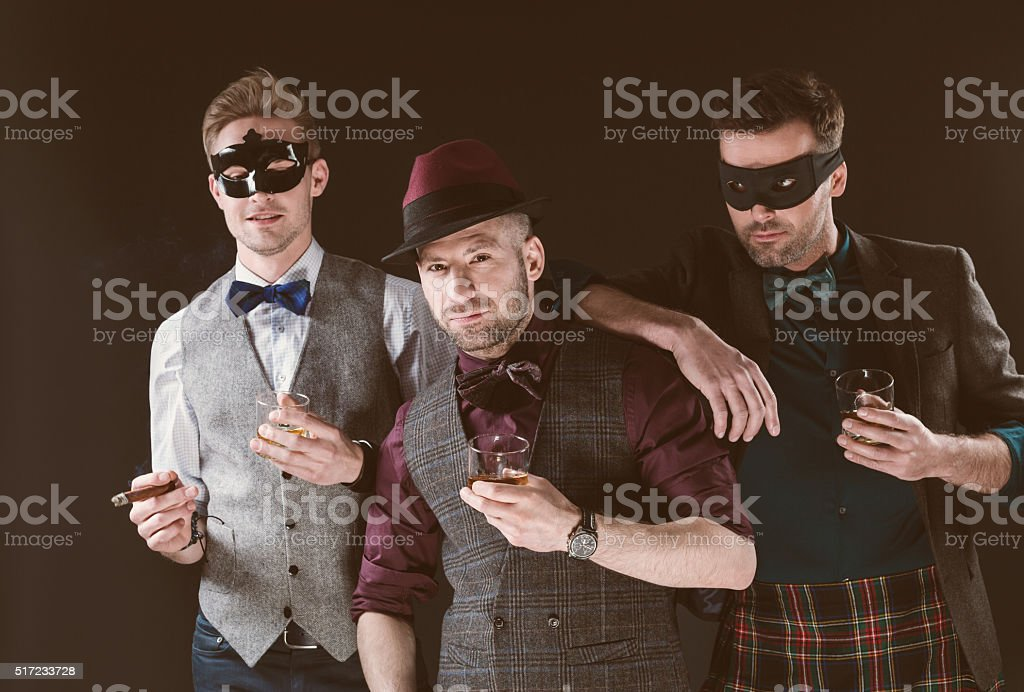 Group of men wearing carnival masks, holding whiskey stock photo