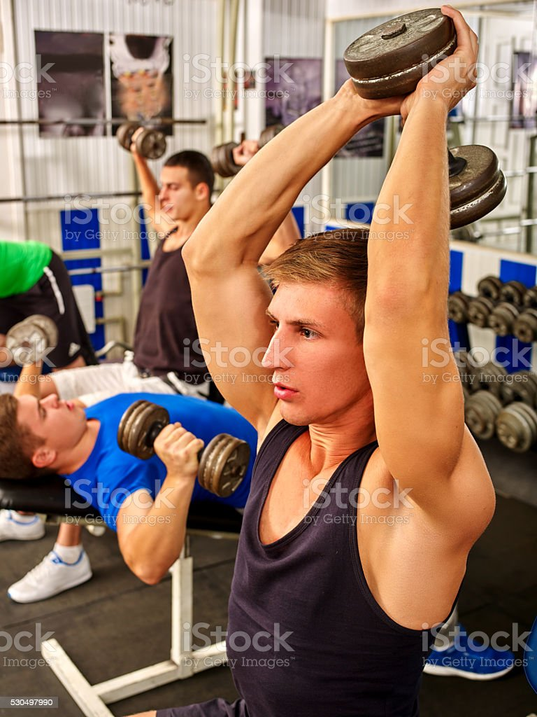 Group of men working his body at gym. stock photo