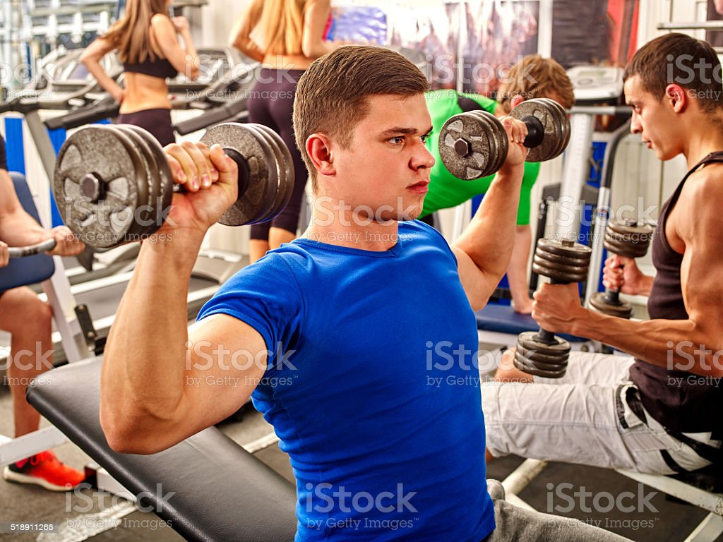 Group of men working with dumbbells  at gym stock photo