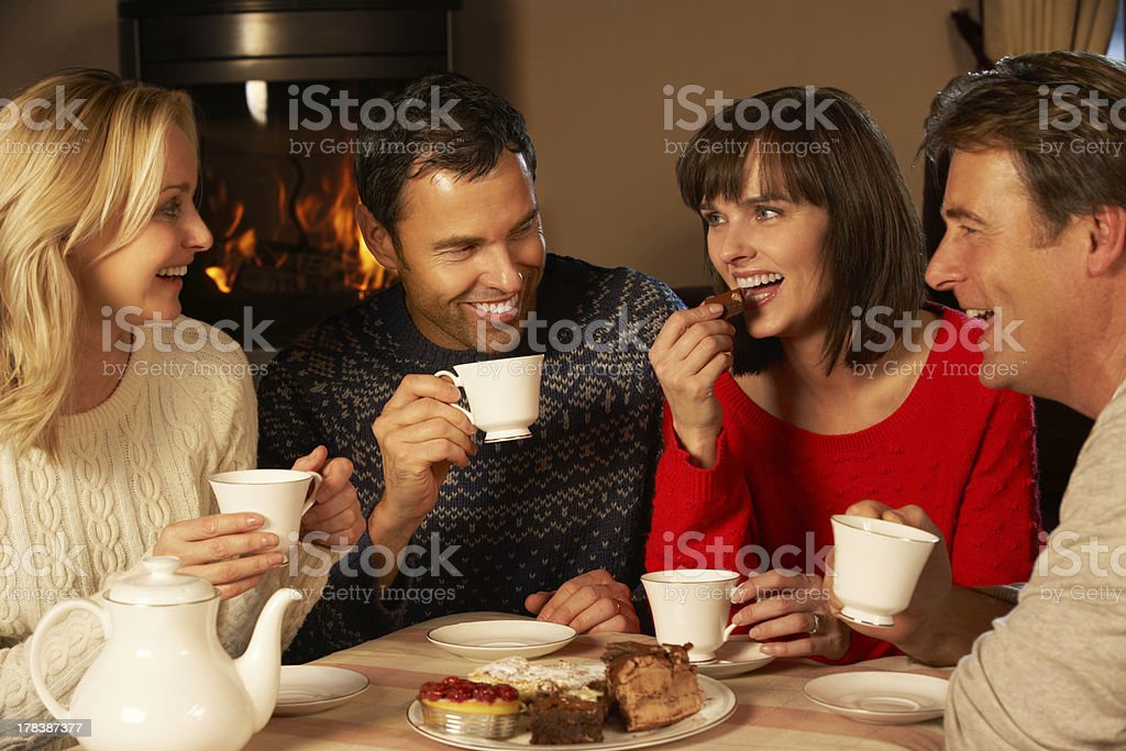 Group Of Middle Aged Couples Enjoying Tea And Cake Together stock photo