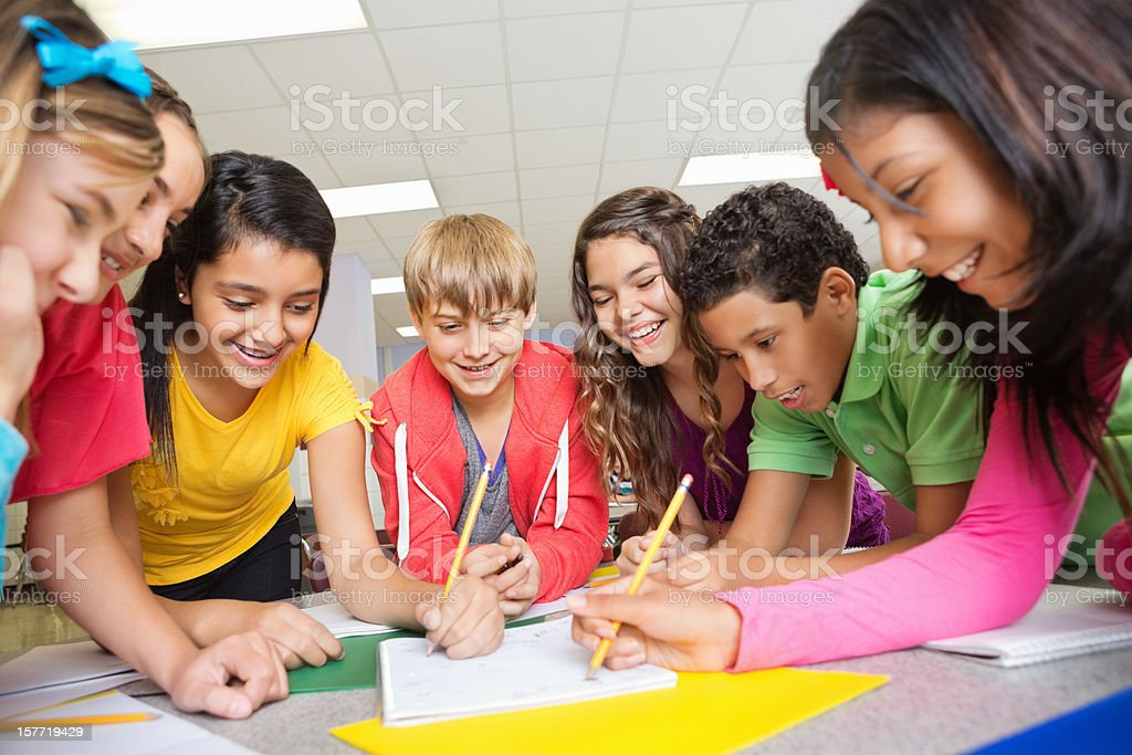 Group of middle school students working on project together royalty-free stock photo