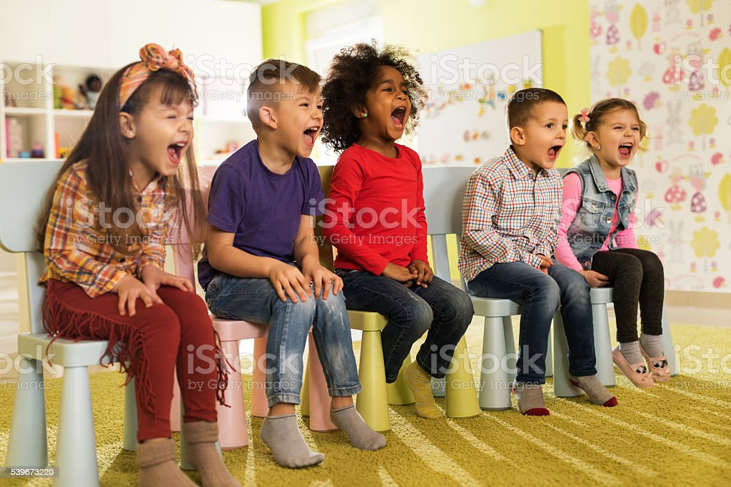 Group of mischief kids sitting at preschool and screaming. stock photo