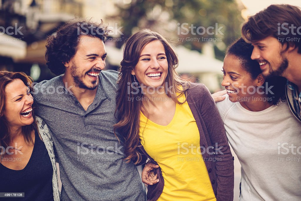 Group of mixed race young people smiling outdoors stock photo