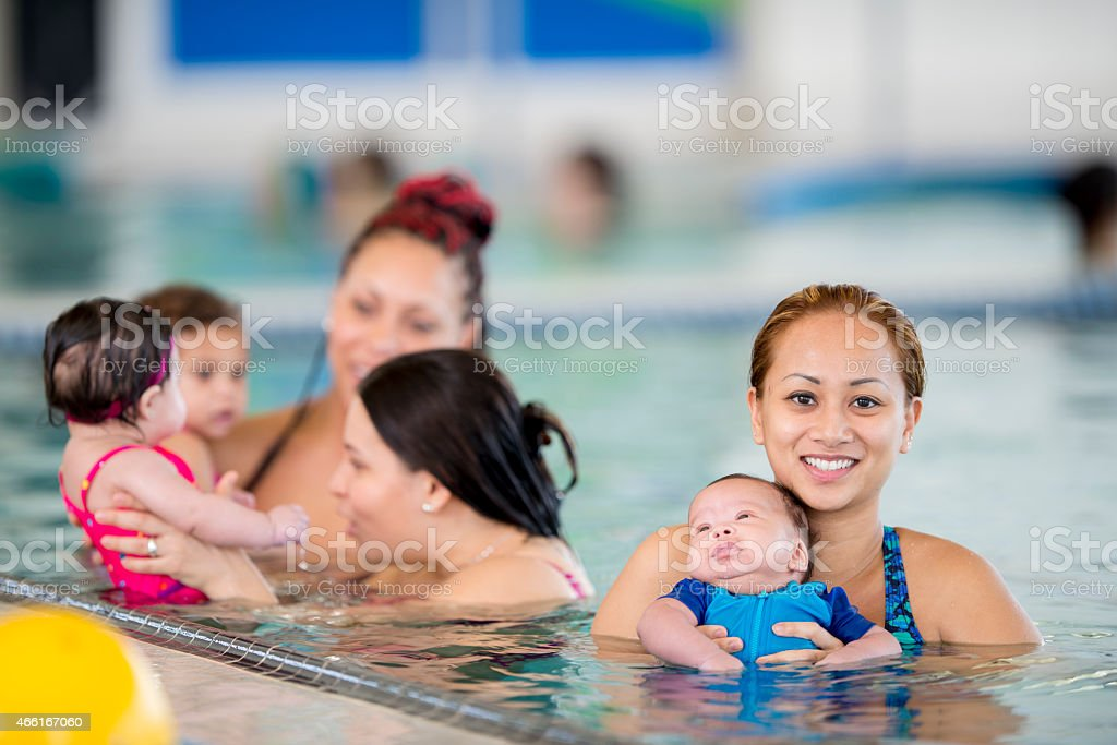 Group of mothers swimming with their babies stock photo