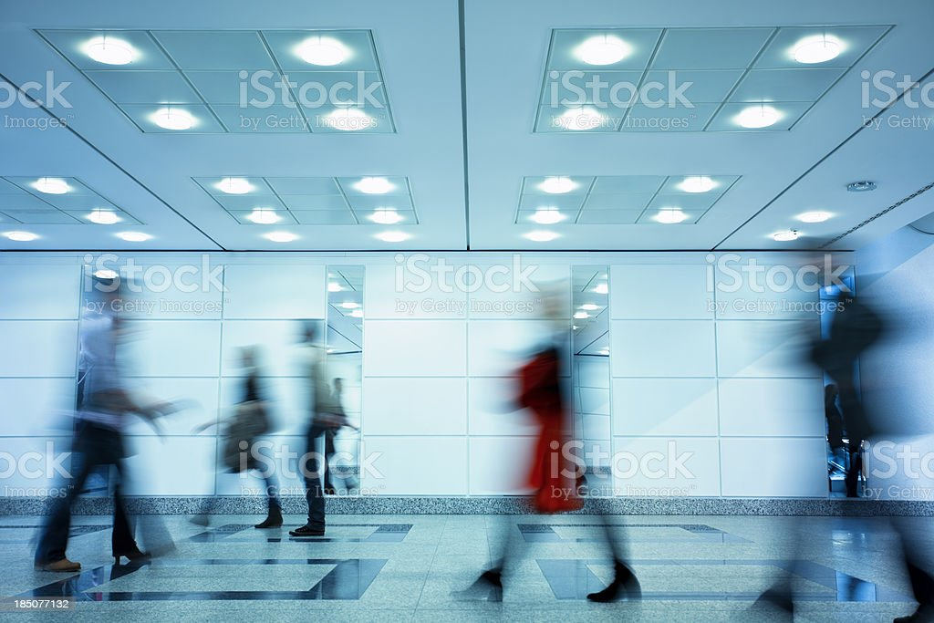 Group of Motion Blurred People Walking Through Illuminated Corridor stock photo