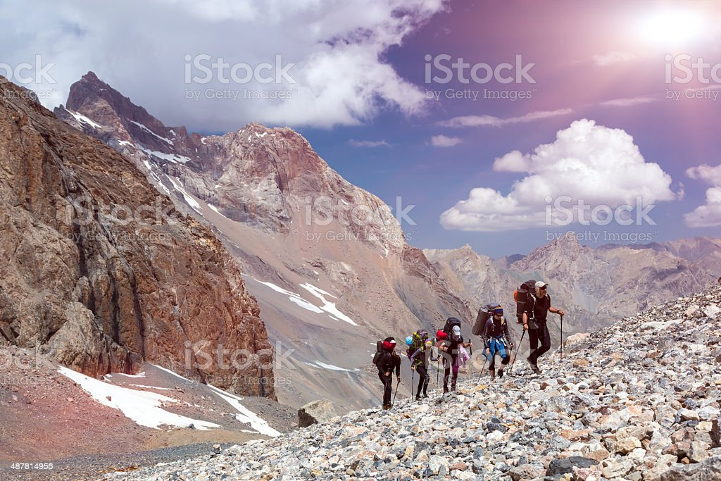 Group of Mountaineer Walking on Deserted Rocky Terrain stock photo