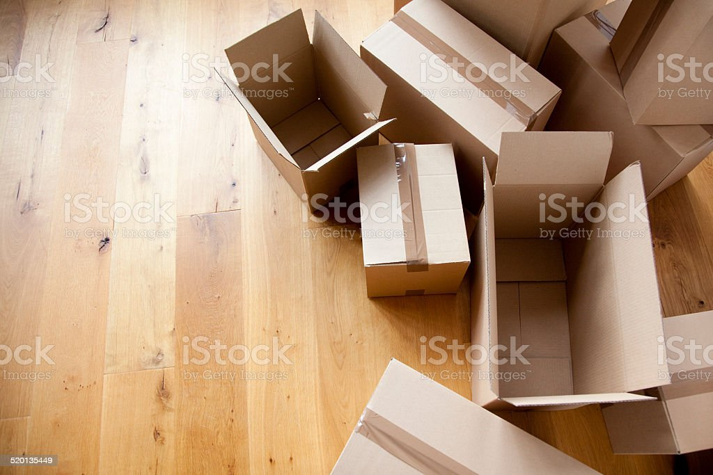 Group of moving boxes on a wooden floor stock photo