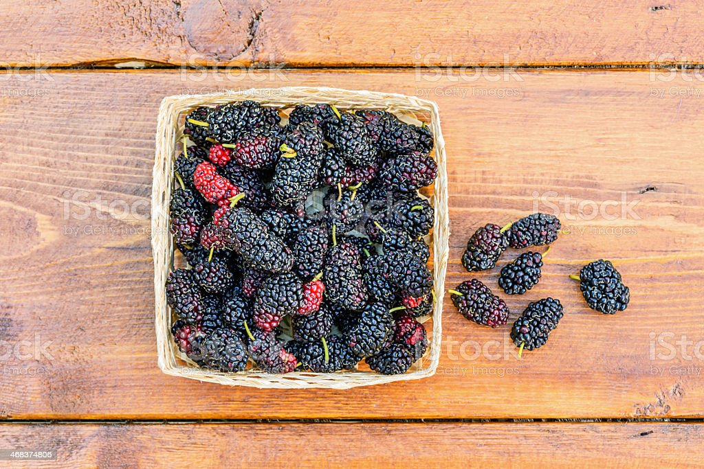 Group of mulberries isolated on wood background. stock photo