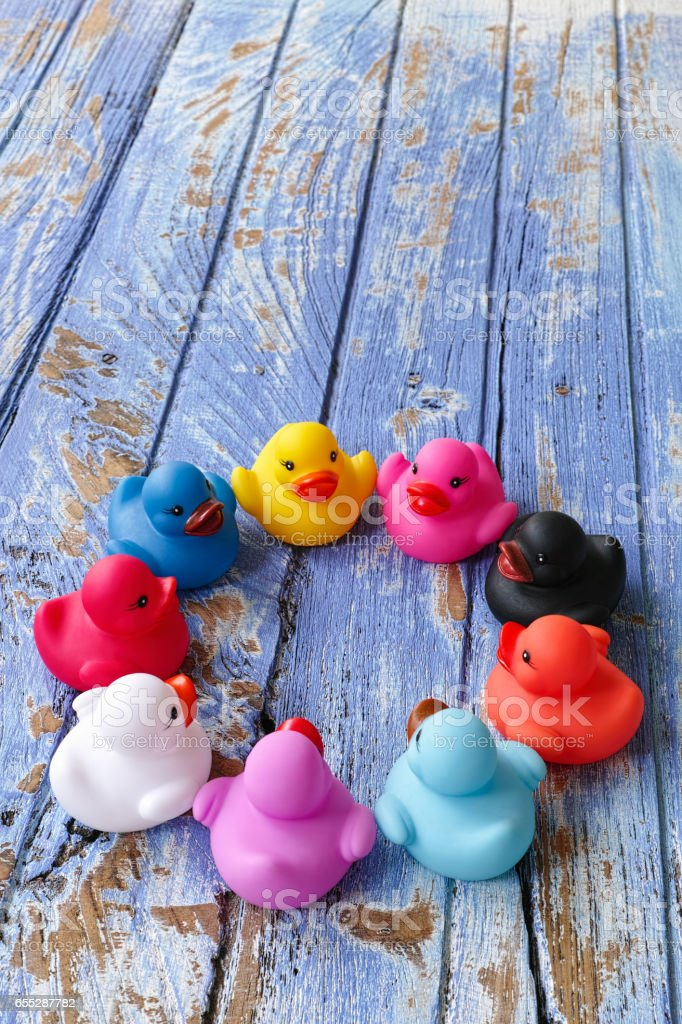 Group of multi-colored rubber ducks sit together in a circle on an old wooden blue table. stock photo