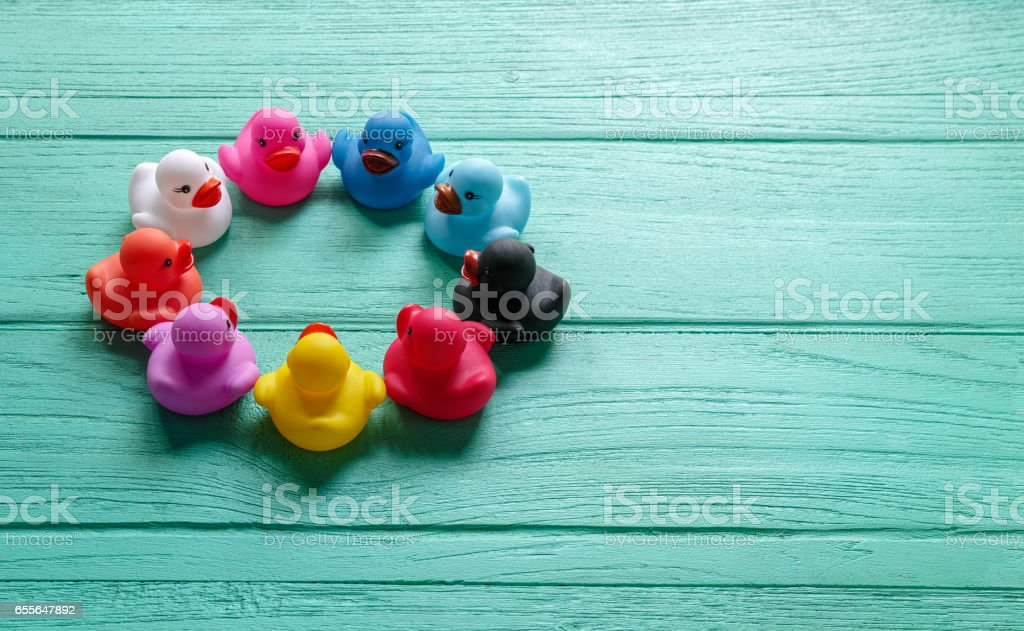 Group of multi-colored rubber ducks sit together in a circle on an old wooden turquoise coloured table. stock photo