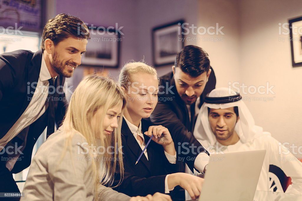 Group of multicultural business professional Using A Lopptp. stock photo